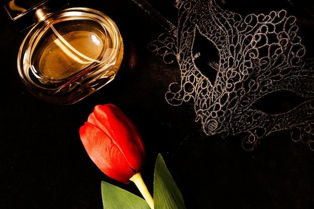 Венецианская маска с красным тюльпаном и духами в темном, многозначительно освещенном помещении. загадочная концепция любви, день святого валентина.