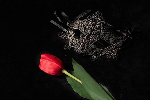 어둡고 암시 적으로 조명 된 환경에서 빨간 튤립이있는 베네치아 마스크. 신비한 사랑 개념, san valentin의 날.