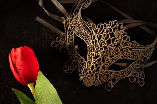 Венецианская маска с красным тюльпаном в темном, многозначительно освещенном помещении. загадочная концепция любви, день святого валентина.