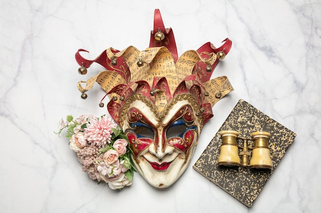 Venetian mask with a book and theater binoculars on a marble table