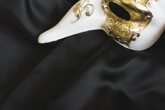 Venetian mask with a long nose on a dark cloth