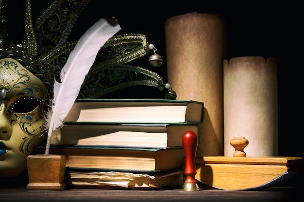 古いインクつぼ、羽、羽、巻物、書籍、木製のテーブルのシールとベネチアンマスク。ヴィンテージの静物画。