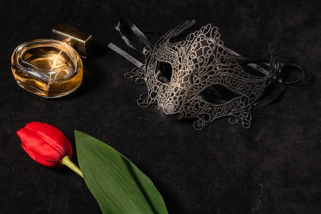 Venetian mask with a red tulip and perfume in a dark, suggestively lit environment. mysterious love concept, san valentin day.