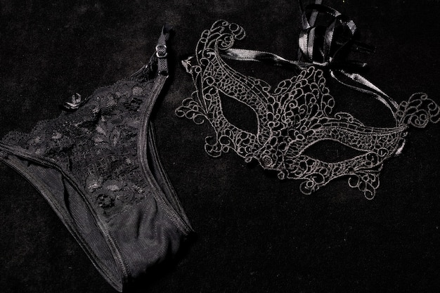 Venetian mask for a woman accompanying black female underwear on a black surface. concept of romanticism, mystery.