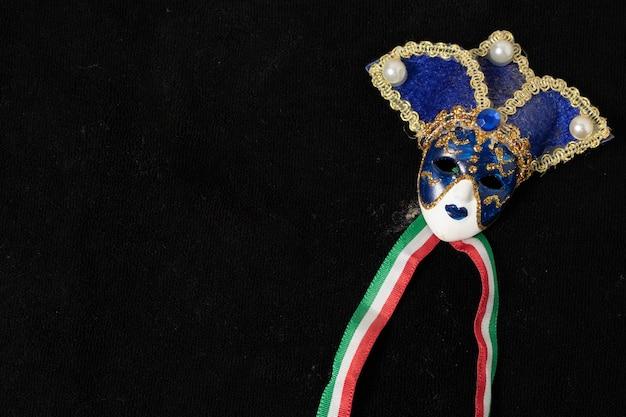 황금 또는 금색 하이라이트가있는 흰색과 검은 색 세라믹 장식의 베네치아 마스크. 검정색 배경.