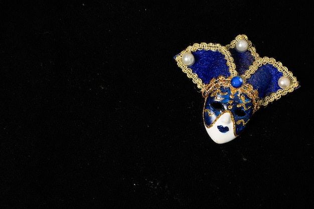 Venetian masks of white and black ceramic ornament with golden or gold highlights. black background.