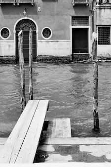 Venetian view with canal and small jetty, venice, italy. black and white