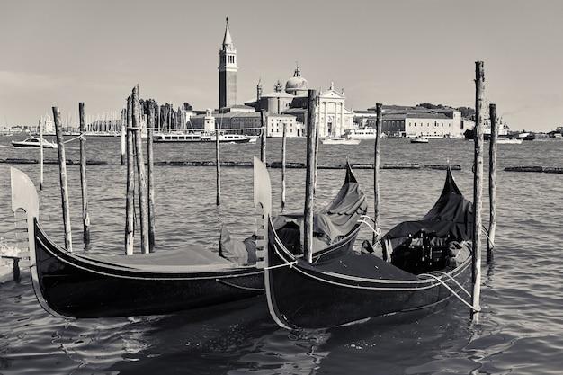 イタリア、ヴェネツィアのゴンドラとサンジョルジョマッジョーレ島のあるヴェネツィアの景色。風景、白黒写真