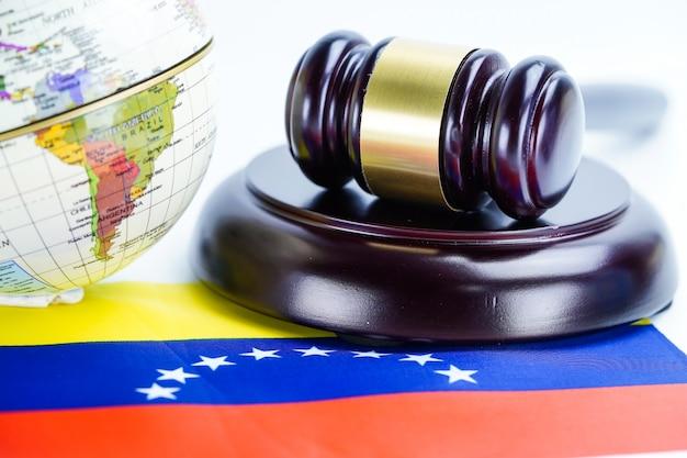 世界の世界地図とベネズエラの旗そして裁判官のハンマー