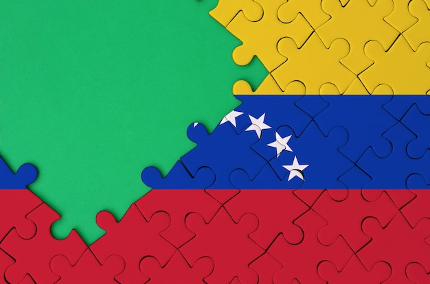 Venezuela flag  is depicted on a completed jigsaw puzzle with free green copy space on the left side