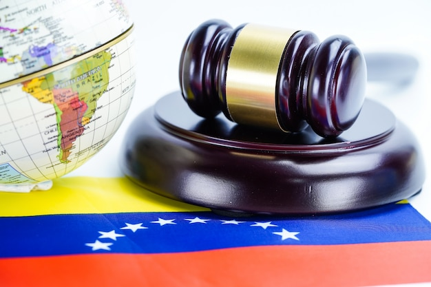 Venezuela flag and judge hammer with globe world map