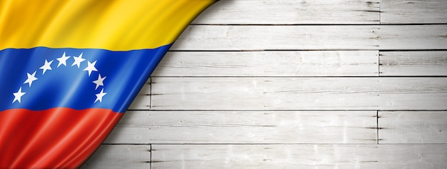 Venezuela flag on old white wall. horizontal panoramic banner.