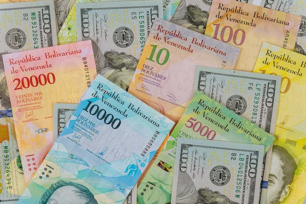 Венесуэльский боливар банкноты с бумажными банкнотами разной валюты.