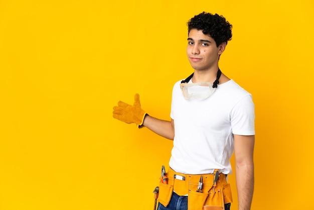 Мужчина-электрик из венесуэлы изолирован на желтом фоне, протягивая руки в сторону для приглашения приехать