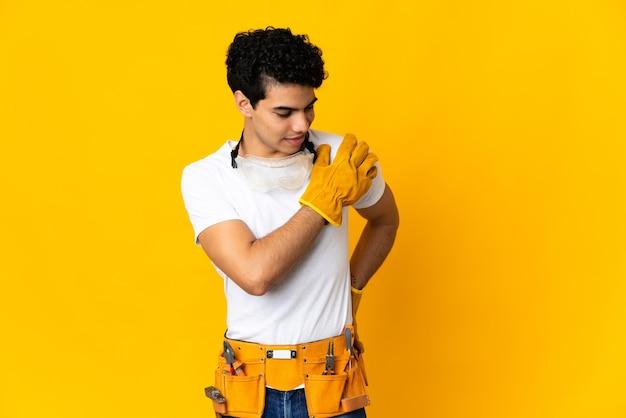 Мужчина-электрик из венесуэлы изолирован на желтом фоне и страдает от боли в плече из-за того, что приложил усилие