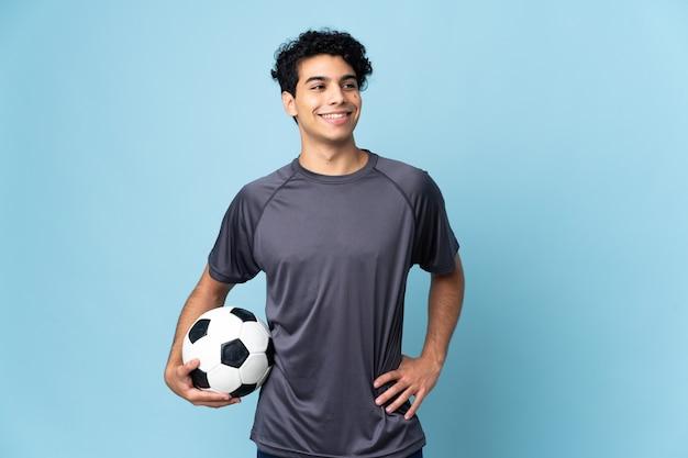 腰に腕を組んでポーズをとって笑顔のベネズエラのサッカー選手の男