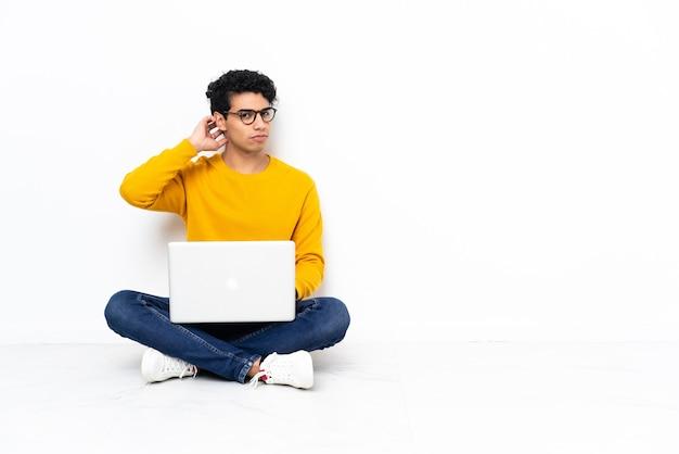 Venezuelan man sitting on the floor with laptop having doubts