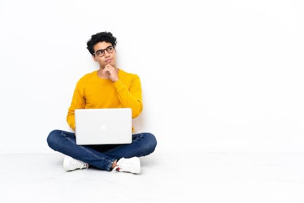 Венесуэльский мужчина сидит на полу с ноутбуком и смотрит вверх