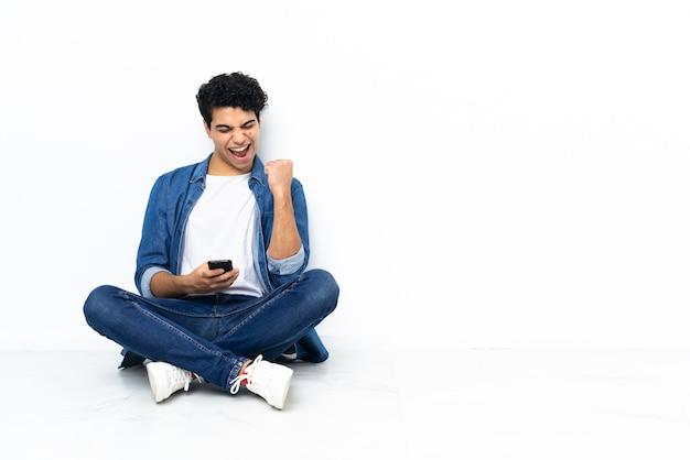 勝利の位置に電話で床に座っているベネズエラの男