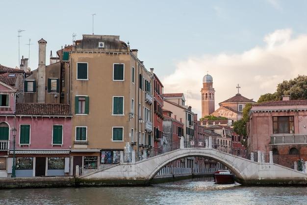 古い中世の建物のカラフルなファサードがある大運河に架かる豪華な橋があるヨーロッパの人気のある観光地としてのヴェネツィア