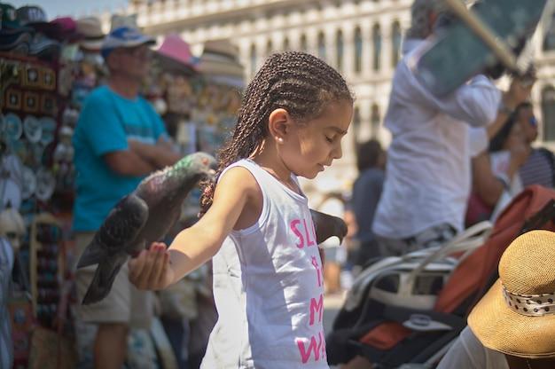 베니스, 이탈리아 2019년 3월 25일: 어린 소녀가 베니스에서 비둘기를 손에 들고 있습니다.