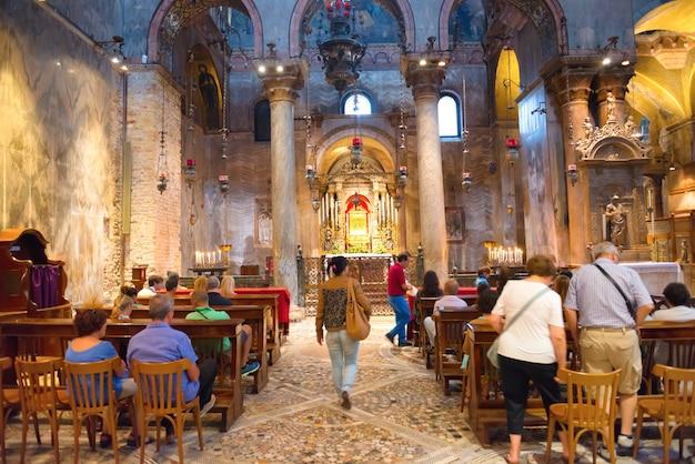 ヴェネツィア、イタリア-2014年8月15日:イタリア、ヴェネツィアの人々とサンマルコ寺院の教会の通路のあるインテリア