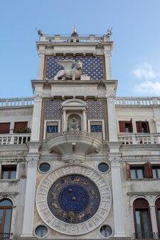 イタリア、ヴェネツィア-2018年7月1日:ヴェネツィアの時計塔のクローズアップファサードは、サンマルコ広場の北側にある初期のルネッサンス様式の建物です