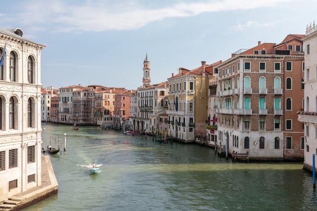 베니스, 이탈리아 - 2018년 7월 1일: 리알토 다리에서 대운하(그란데 운하)의 탁 트인 전망. 베니스 시의 주요 수상 교통 회랑입니다. 여름 화창한 날과 푸른 하늘의 풍경