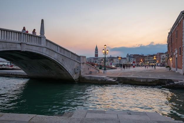 Венеция, италия - 1 июля 2018: панорамный вид на побережье лагуна венета в венеции с мостом. пейзаж летнего вечернего дня с красочным голубым и розовым небом. люди ходят и отдыхают