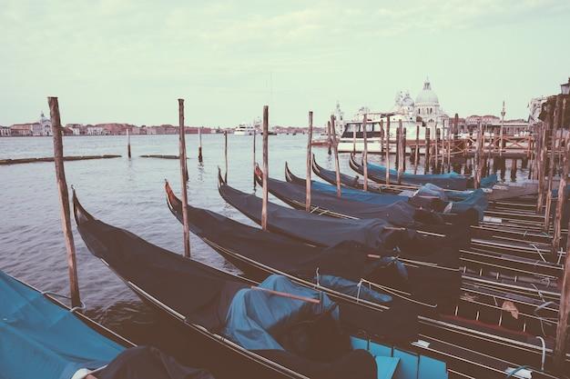Венеция, италия - 1 июля 2018: панорамный вид на побережье лагуна венета города венеции с гондолами. пейзаж летнего утреннего дня и драматического голубого неба