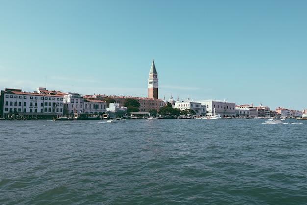 Венеция, италия - 1 июля 2018: панорамный вид на побережье венеции с историческими зданиями и лагуной венета с движением лодок. пейзаж летнего солнечного дня и голубого неба