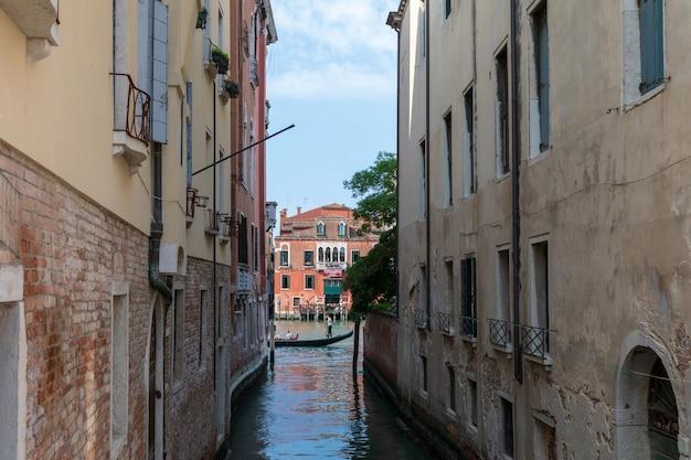 Венеция, италия - 1 июля 2018: панорамный вид на узкий канал венеции с историческими зданиями и лодками с моста. пейзаж летнего солнечного дня