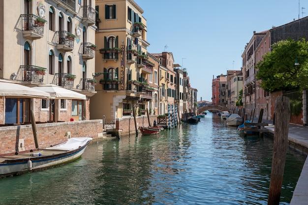 베니스, 이탈리아 - 2018년 7월 1일: 역사적인 건물과 다리에서 보트가 있는 베니스 좁은 운하의 탁 트인 전망. 여름 화창한 날의 풍경