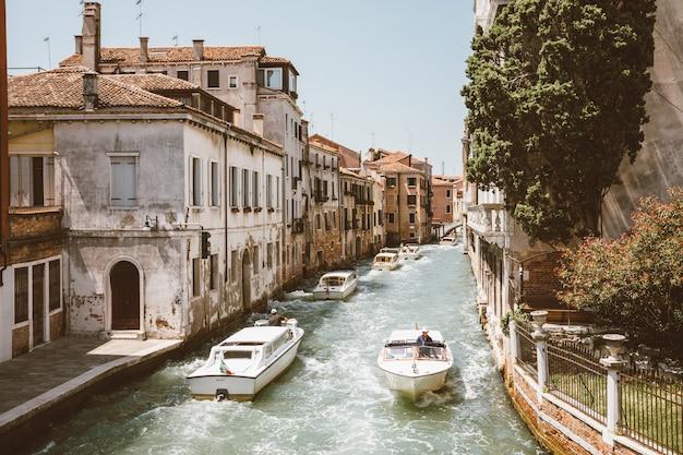 Венеция, италия - 1 июля 2018: панорамный вид на узкий канал венеции с историческими зданиями и движением лодок от моста фоскари. пейзаж летнего солнечного дня и голубого неба