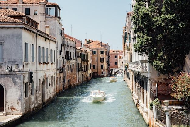 이탈리아 베니스 - 2018년 7월 1일: 포스카리 다리(bridge foscari)에서 역사적인 건물과 보트 교통이 있는 베니스 좁은 운하의 탁 트인 전망. 여름 화창한 날과 푸른 하늘의 풍경