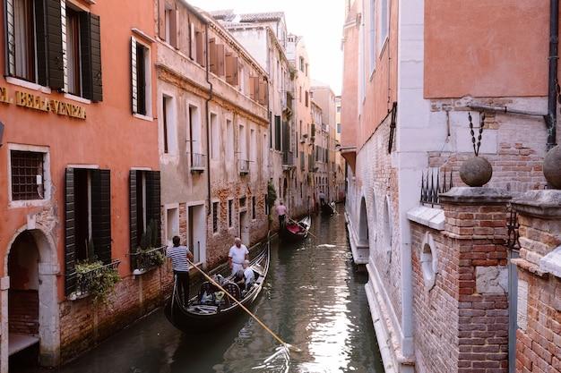 베니스, 이탈리아 - 2018년 7월 2일: 다리에서 역사적인 건물과 곤돌라가 있는 베니스 좁은 운하의 탁 트인 전망. 가수는 곤돌라에서 노래합니다. 여름 화창한 날과 일몰 하늘