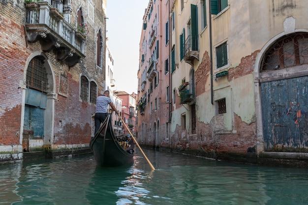 イタリア、ヴェネツィア-2018年7月2日:他のゴンドラからの歴史的な建物やゴンドラがあるヴェネツィアの狭い運河のパノラマビュー。人々はゴンドラでリラックスします。夏の晴れた日と夕焼け空