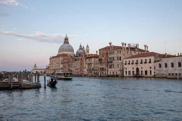 Venice, italy - june 30, 2018: panoramic view of venice grand canal view with historical buildings, gondola and boats, away of basilica salute. landscape of summer evening day and colorful sky