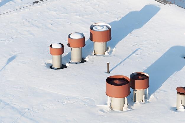 Вентиляционные трубы на крыше. плоская крыша полностью засыпана снегом.