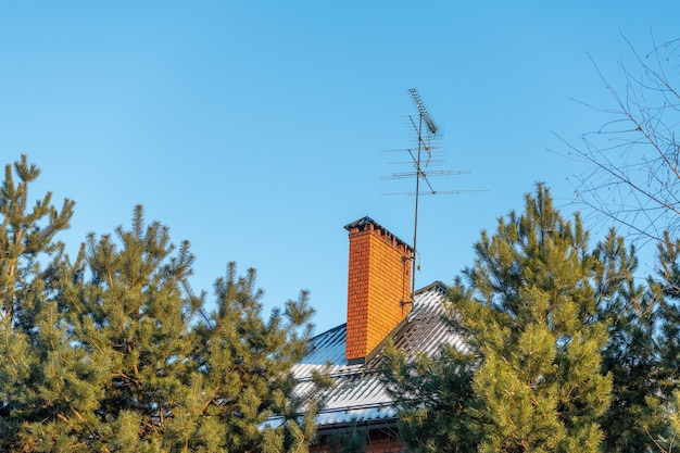 Ventilation or chimney pipe from orange bricks on a snowy roof of a country house with tv antennas on blue sky