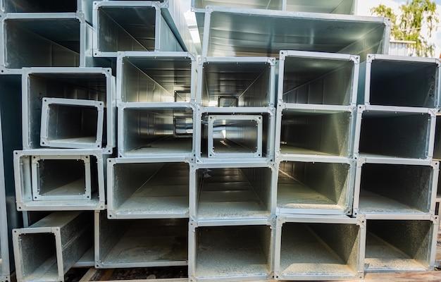 Склад вентиляционных труб. трубы стальные, детали для строительства воздуховодов промышленной системы кондиционирования на складе. промышленное вентиляционное оборудование и трубопроводные системы.