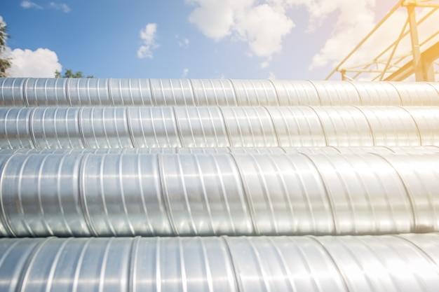 Вентиляционные трубы против голубого неба. трубы стальные, детали для строительства воздуховодов промышленной системы кондиционирования на складе. промышленное вентиляционное оборудование.