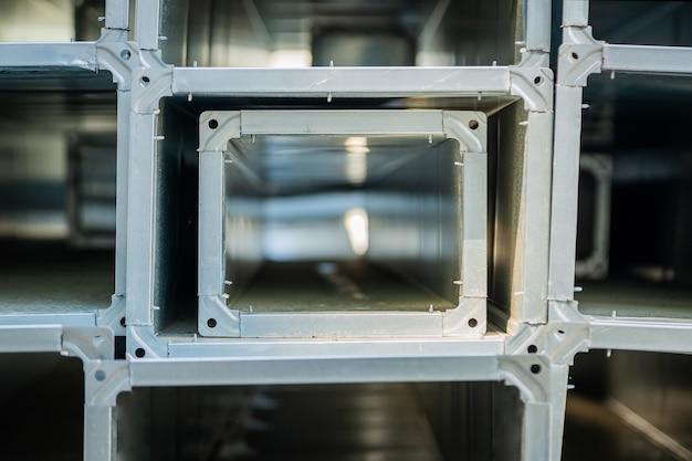 Вентиляционные трубы бывают квадратными и прямоугольными. трубы стальные, детали для строительства воздуховодов промышленной системы кондиционирования на складе. промышленное вентиляционное оборудование.