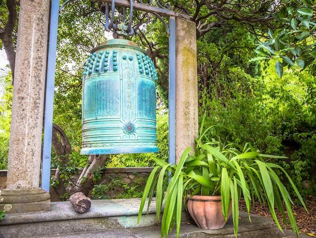 Вентимилья, италия - около августа 2020 года: старинный японский колокол, расположенный в садах хамбери и искусно выполненный из бронзы. похоже, что это из буддийской святыни, разрушенной пожаром в центральной японии.