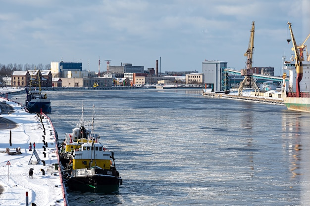 Ventspils, latvia, february 6, 2021: two tugs in the port canal, industrial background