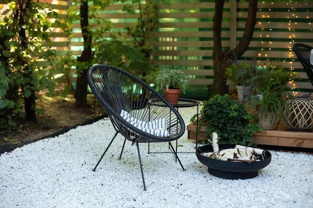 庭に黒いアカプルコのアームチェアテーブルと金属製の黒い暖炉のボウルが付いている家のベランダ