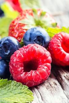 라즈베리, 딸기, 신 블루베리, 사랑스러운 향기로운 민트로 구성된 제철 과일의 세로 사진.