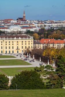 オーストリアのウィーンにあるシェーンブルン宮殿の建物の半分と、秋の日の青い空を背景にした他の歴史的な家屋の屋根のある垂直の街並み。
