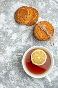 Vista verticale di una tazza di tè nero con limone e biscotti deliziosi sulla superficie del ghiaccio