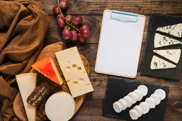 Verity of cheese; grapes and silk textile with black clipboard